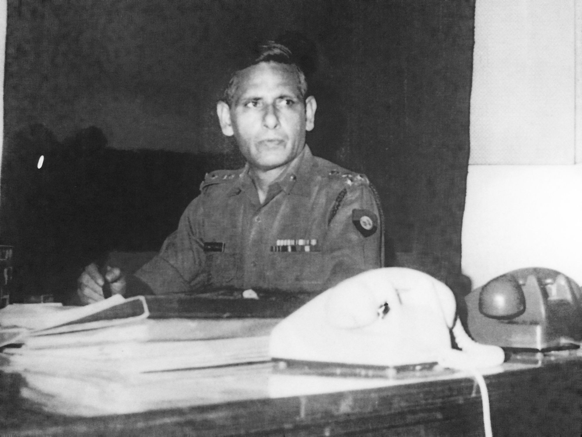Shiv Bhattacharjya in military uniform at a desk with two telephones