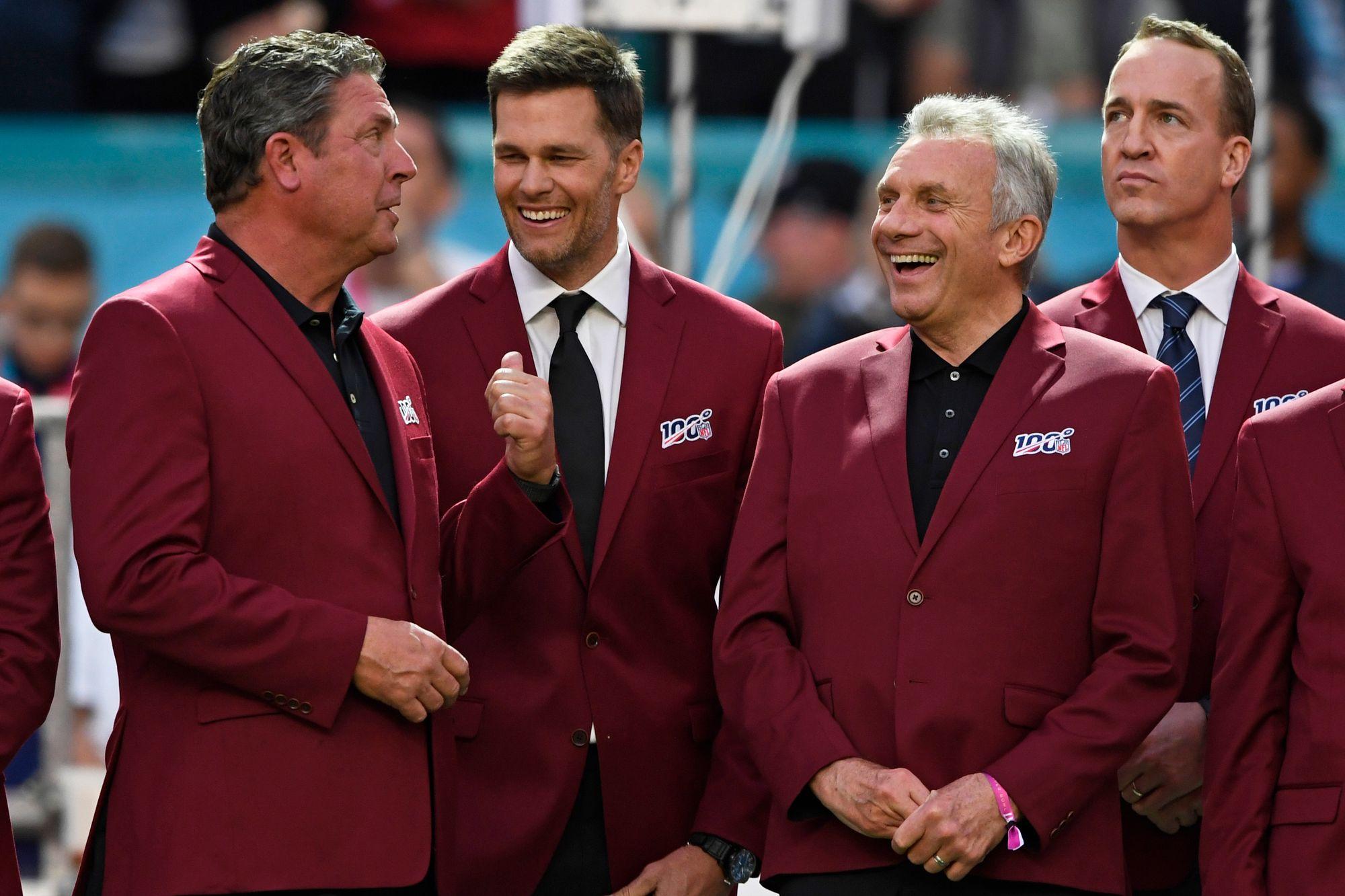 Dan Marino, Tom Brady, Joe Montana laughing,  Peyton Manning in background